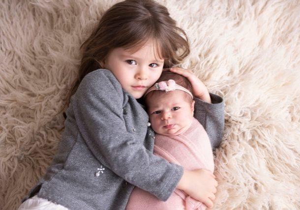 ensaio newborn com irmãos mais velhos irmão segura bebê recém nascida em fotos fofas fotógrafa laura alzueta