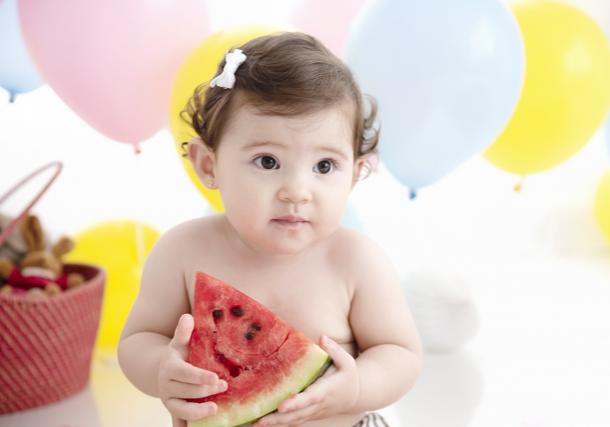 bebê com fatia de melancia menina fofa fundo com balão de frutas smash the fruit aniversário de 1 ano de criança fotos de família no estúdio de fotografia laura alzueta em São Paulo